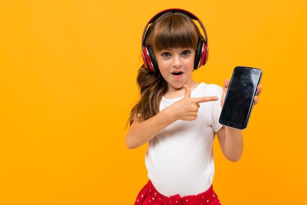 Retrato de uma encantadora menina caucasiana com longos cabelos castanhos e rosto bonito, com um vestido branco e vermelho, ouvir música com grandes fones de ouvido vermelhos e sorrisos