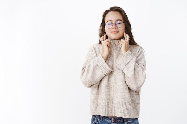 Retrato de uma encantadora menina sonhadora fazendo um desejo com os dedos cruzados para dar boa sorte e olhos fechados Foto gratuita