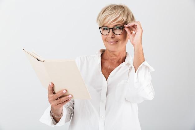 Retrato de uma encantadora mulher adulta usando óculos, lendo um livro isolado sobre uma parede branca em estúdio