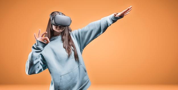 Retrato de uma encantadora mulher de cabelos castanhos usando óculos de realidade virtual em um fundo laranja