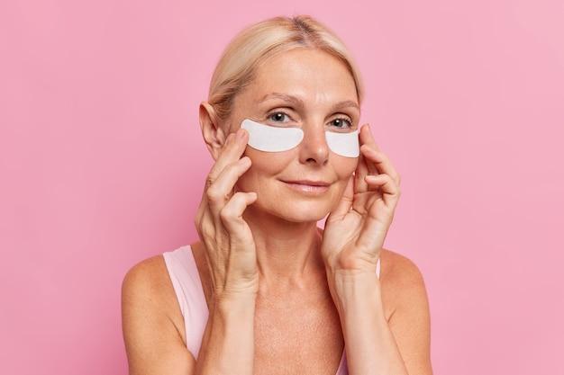 Retrato de uma encantadora mulher de meia-idade com cabelo claro aplica manchas brancas sob os olhos para reduzir as rugas, olheiras e linhas finas usa poses mínimas de maquiagem contra a parede rosa