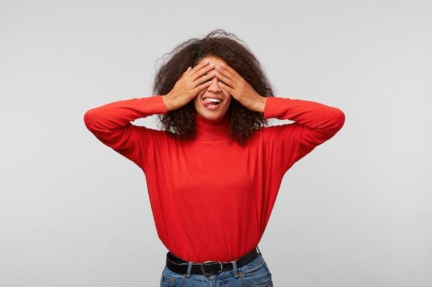 Retrato de uma encantadora mulher feliz com um penteado afro cobrindo os olhos com as palmas das mãos e sorrindo amplamente de alegria
