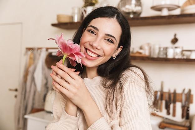 Retrato de uma encantadora mulher morena sorrindo e segurando uma bela flor em casa
