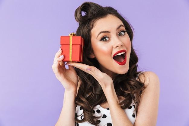 Retrato de uma encantadora mulher pin-up em um vestido vintage de bolinhas sorrindo enquanto segura uma caixa de presente vermelha isolada sobre a parede violeta