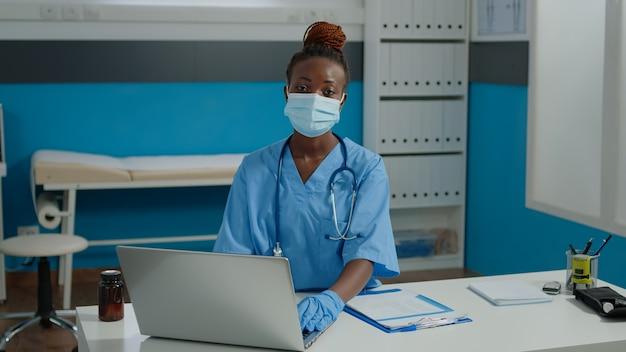 Retrato de uma enfermeira sentada na mesa e usando o laptop