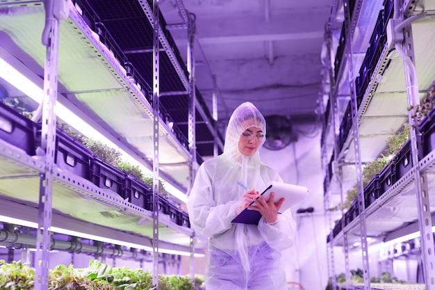 Retrato de uma engenheira agrícola escrevendo na área de transferência em pé entre as prateleiras na estufa do viveiro de plantas iluminada por uma luz azul, copie o espaço