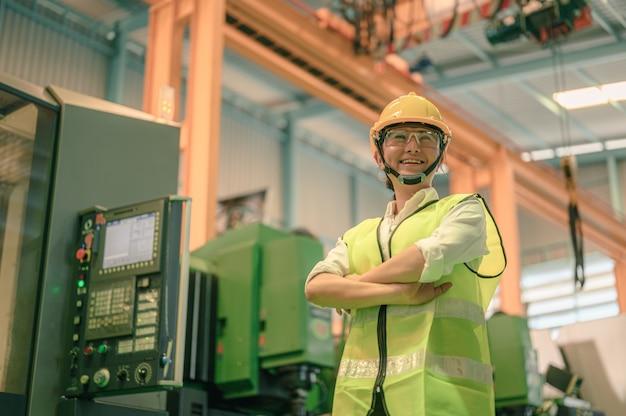 Retrato de uma engenheira usando um capacete e óculos de segurança em uma planta industrial