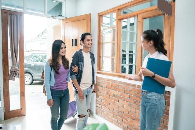 Retrato de uma equipe asiática de hospedagem dando boas-vindas a um casal em um hotel boutique