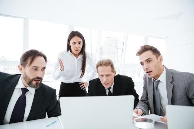 Retrato de uma equipe de negócios chocada ao lado da mesa, olhando para o laptop no escritório