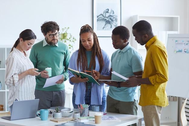 Retrato de uma equipe de negócios multiétnica contemporânea em pé junto à mesa no escritório ouvindo uma líder afro-americana