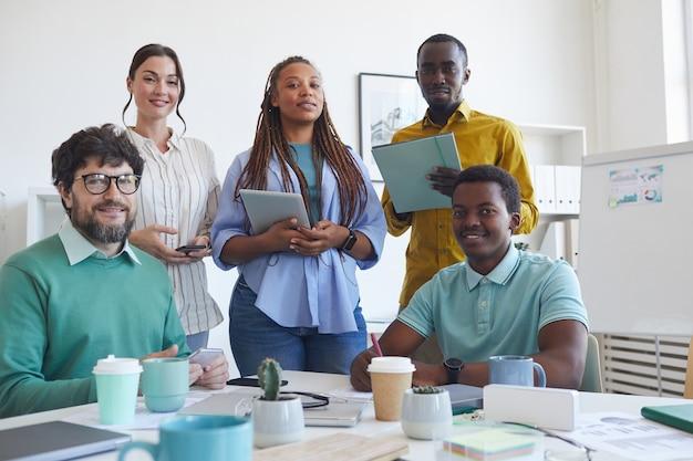 Retrato de uma equipe de negócios multiétnica enquanto posava na sala de conferências durante a reunião