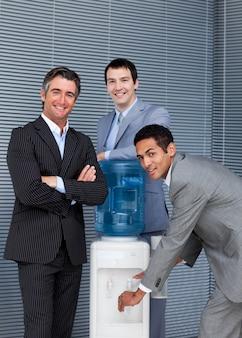 Retrato de uma equipe de negócios que enche o copo do refrigerador de água