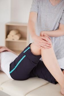 Retrato de uma esportista com uma massagem no joelho