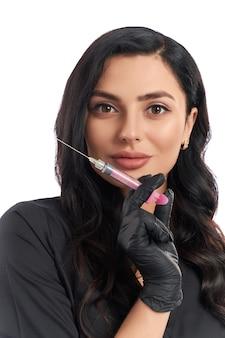 Retrato de uma esteticista atraente de uniforme e luvas de borracha segurando uma seringa para procedimentos de cuidados com a pele