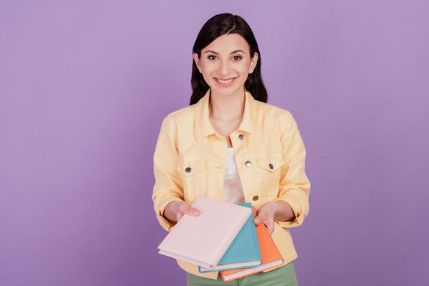Retrato de uma estudante adorável segurando um caderno de pilha em fundo roxo
