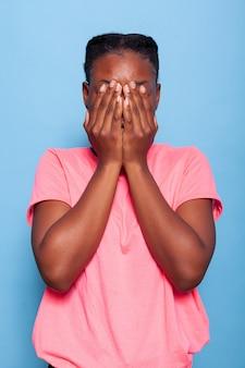 Retrato de uma estudante afro-americana emocional e ansiosa, cobrindo o rosto com as mãos