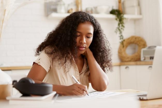 Retrato de uma estudante afro-americana séria concentrada segurando um lápis, escrevendo, se preparando para os exames ou fazendo a lição de casa na cozinha, sentada à mesa de jantar com um laptop aberto e livros