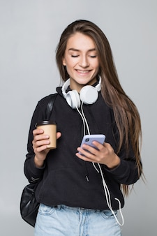 Retrato de uma estudante atraente alegre com mochila, ouvindo música com fones de ouvido enquanto mostra o telefone móvel de tela em branco e dança isolado sobre a parede branca