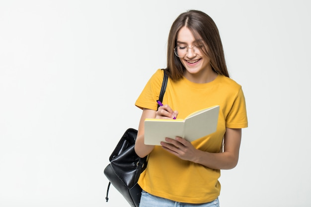 Retrato de uma estudante casual sorridente com mochila, escrevendo em um bloco de notas em pé com os livros isolados sobre a parede branca