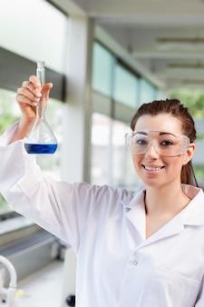 Retrato de uma estudante de ciência feminina segurando um líquido azul