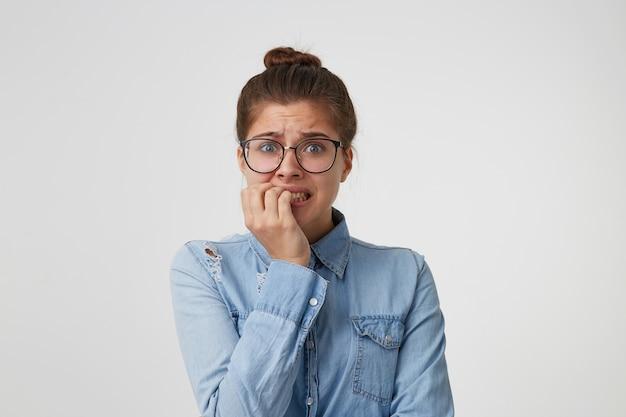 Retrato de uma estudante de óculos, vestida com uma camisa jeans da moda, preocupada com algo