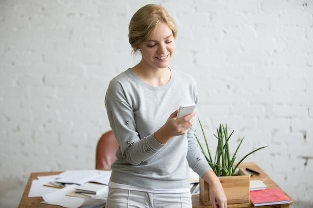 Retrato de uma estudante de pé perto da mesa com um telefone na mão