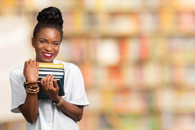 Retrato de uma estudante feliz menina ou mulher com livros na biblioteca