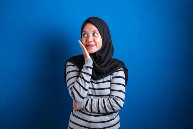 Retrato de uma estudante muçulmana asiática sorrindo e pensando em um gesto, encontrando uma solução para os problemas