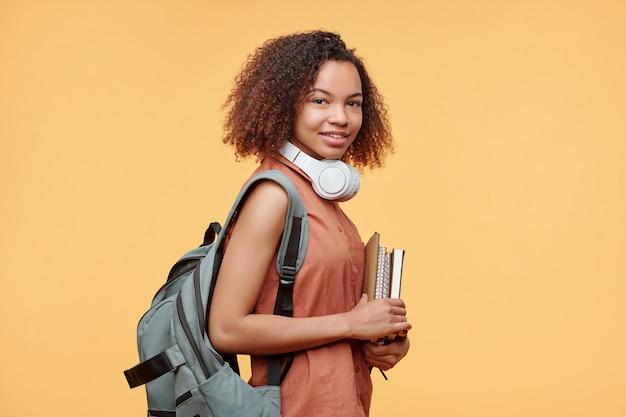 Retrato de uma estudante negra sorridente com penteado afro em pé com pastas de trabalho contra um fundo amarelo