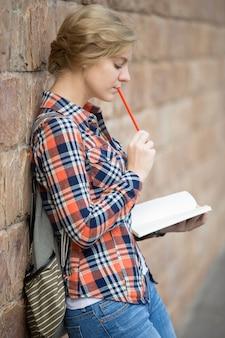 Retrato de uma estudante pensante contra a parede de tijolos, sonhando