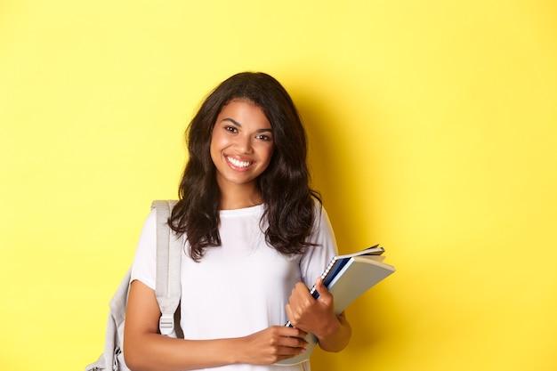 Retrato de uma estudante universitária afro-americana feliz, segurando cadernos e uma mochila, sorrindo e em pé sobre um fundo amarelo