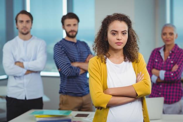 Retrato de uma executiva em pé com seus colegas