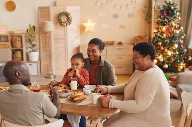 Retrato de uma família afro-americana feliz apreciando chá e lanches enquanto celebra o natal em casa