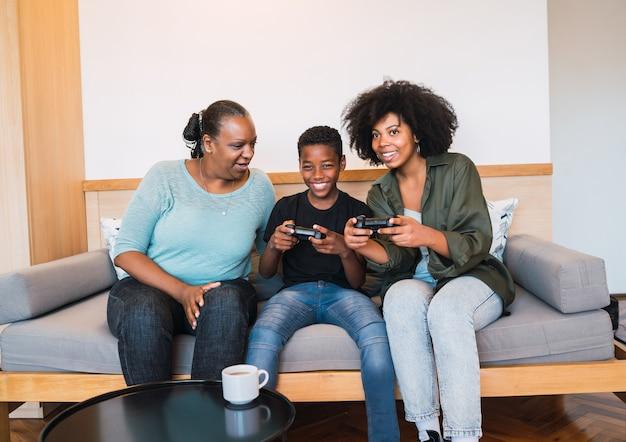 Retrato de uma família afro-americana feliz, sentada no sofá, jogando videogame