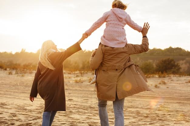 Retrato de uma família alegre com uma filha a passar tempo