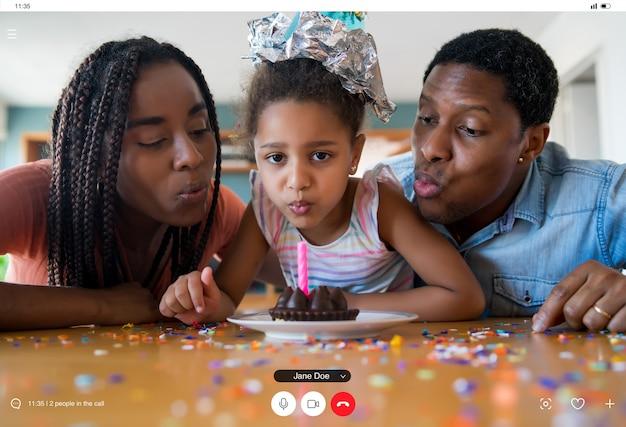 Retrato de uma família comemorando aniversário online em uma videochamada com familiares e amigos enquanto estava em casa. novo conceito de estilo de vida normal.