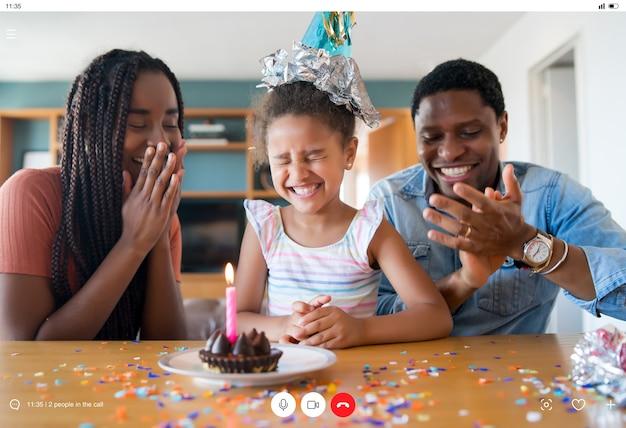 Retrato de uma família comemorando aniversário online em uma videochamada com familiares e amigos enquanto estava em casa.