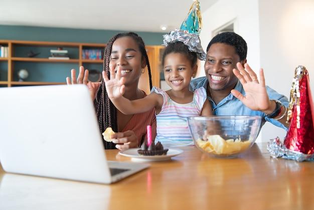 Retrato de uma família comemorando aniversário online em uma videochamada com laptop enquanto estava em casa. novo conceito de estilo de vida normal.