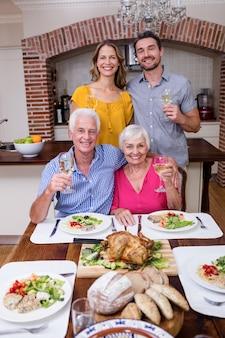 Retrato de uma família de duas gerações, segurando um copo de vinho na mesa