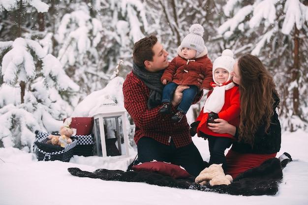 Retrato de uma família elegante, divertindo-se na floresta de inverno. lugar decorado para relaxar.