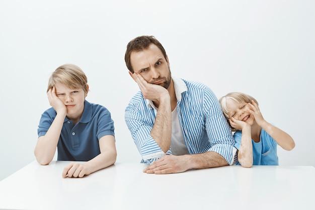 Retrato de uma família engraçada de pai e filhos sentados à mesa, inclinando a cabeça sobre a mão e fazendo caretas