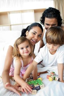 Retrato de uma família feliz brincando com blocos de letras
