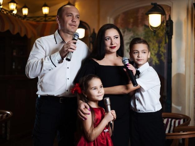 Retrato de uma família feliz, cantando em microfones