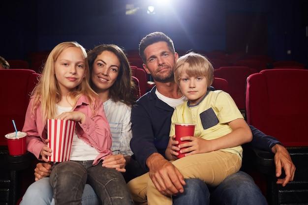 Retrato de uma família feliz com duas crianças olhando para a câmera enquanto espera para assistir um filme no cinema