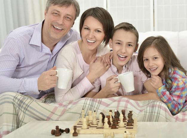 Retrato de uma família feliz jogando xadrez em casa