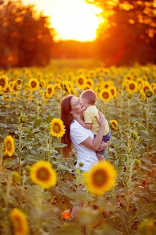 Retrato de uma família feliz, mãe com seu filho em um campo de girassóis