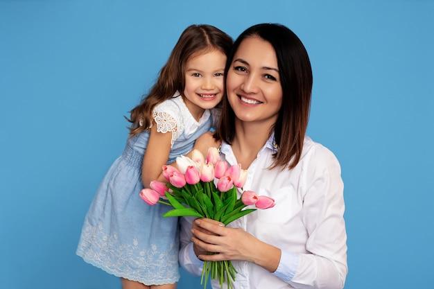 Retrato de uma família feliz. mãe e filha com um sorriso de dentes brancos segurar um buquê de tulipas cor de rosa nas mãos