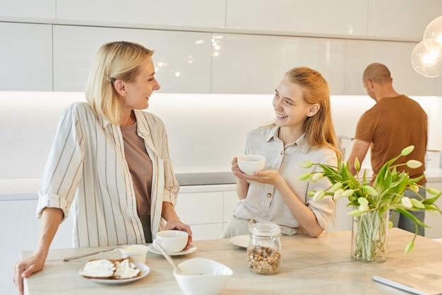 Retrato de uma família feliz moderna na cozinha, foco na mãe sorridente, conversando com a filha adolescente enquanto toma o café da manhã