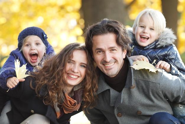 Retrato de uma família feliz no parque outono com folhas de plátano