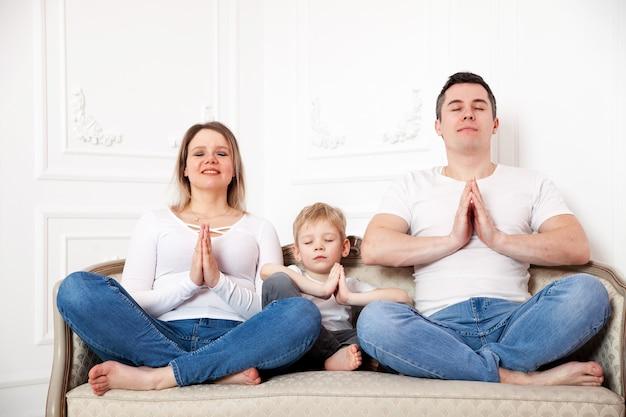 Retrato de uma família fofa com filho meditando na posição de lótus no sofá